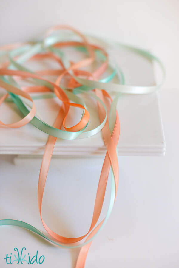 peach and teal hand-painted ribbons on a white surface.
