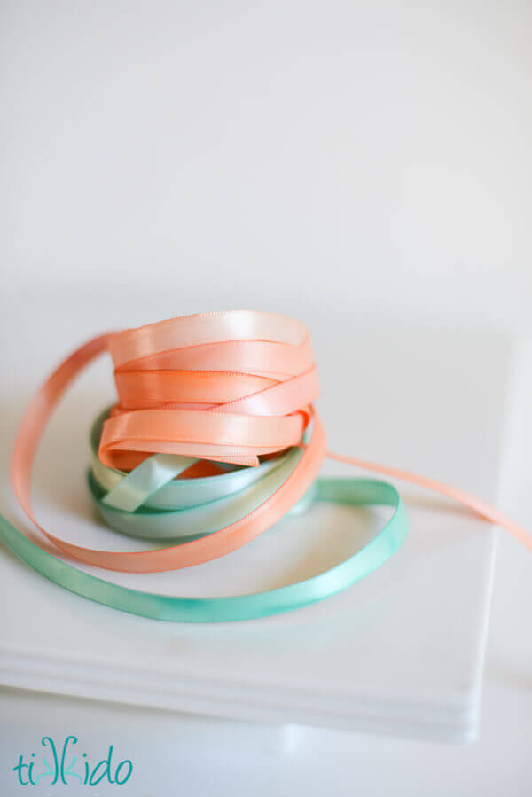 Painted ribbon painted with watercolor paints, coiled and stacked on a white background.