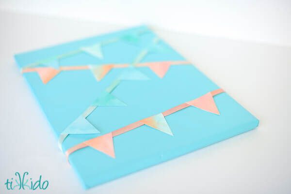 Painted ribbon and watercolor painted paper made into mini bunting used to wrap a present.
