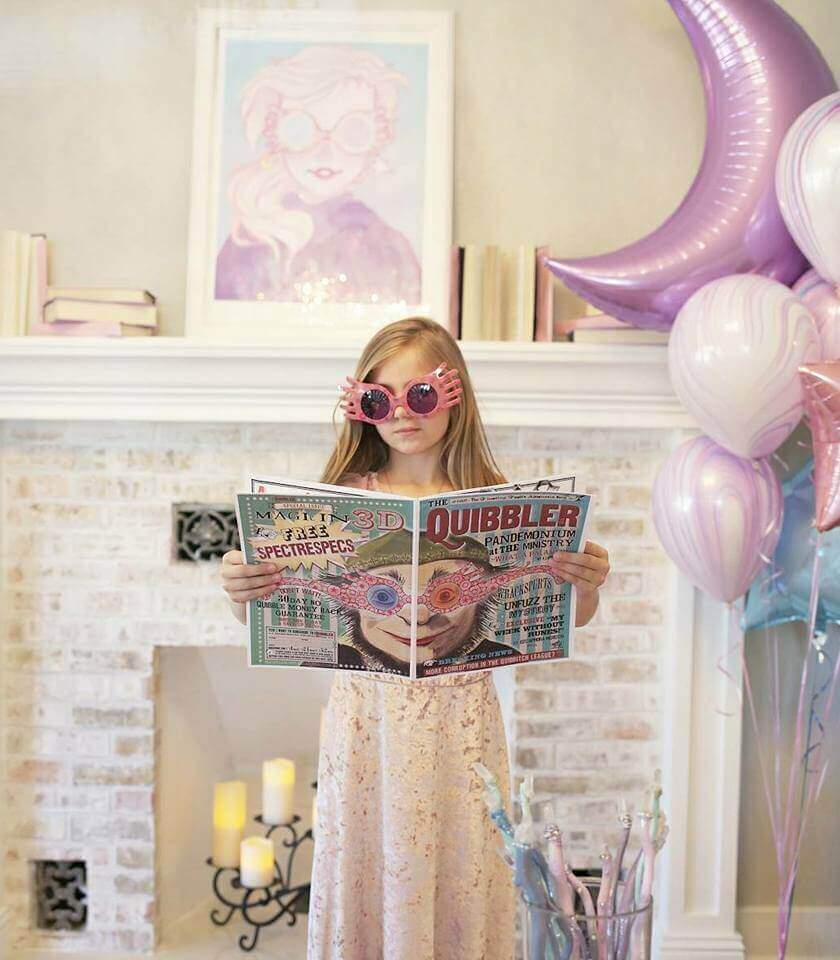 Little girl dressed as Luna Lovegood holding a copy of the Quibbler newspaper.