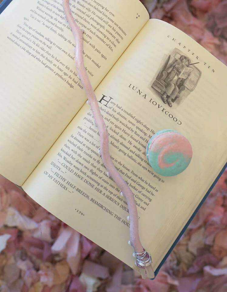 Lavender luna lovegood magic wand with crystal topper and a pink and blue swirled macaron on an open Harry Potter book.