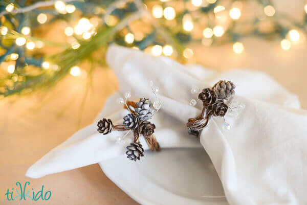 Pine Cone napkin ring with real pinecones and clear Swarovski crystals on a white napkin.