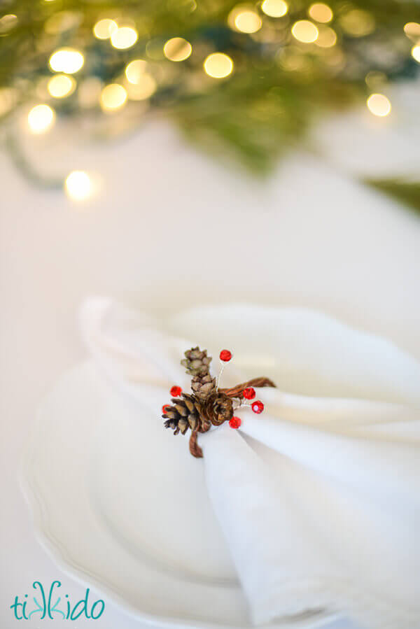 Pinecone napkin ring made with real pine cones and Swarovski crystals on a white napkin.