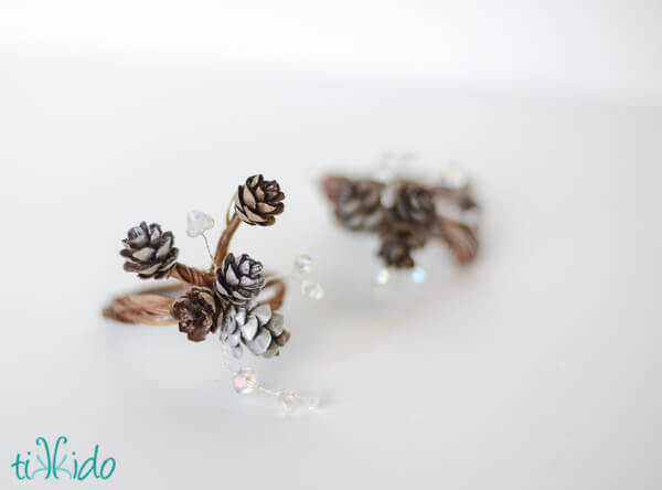 Pinecone napkin rings on a white surface.
