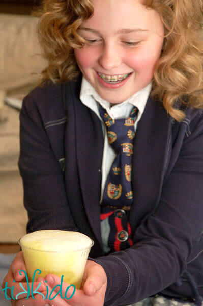 Girl dressed in Harry Potter costume smiling at clear cup filled with foaming yellow liquid.
