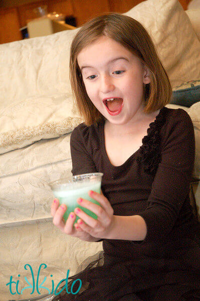 Girl smiling with delight as her clear cup of liquid turns green in her hands.