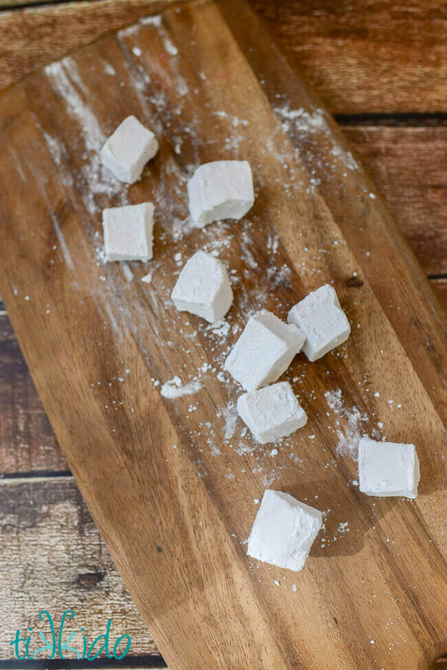 Homemade marshmallows cut into squares and dusted with powdered sugar on a wooden cutting board.