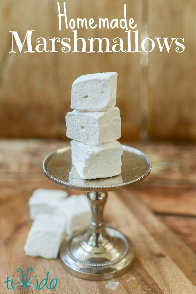 Three homemade marshmallows stacked on a tiny serving tray, and three more homemade marshmallows on the wooden surface below.