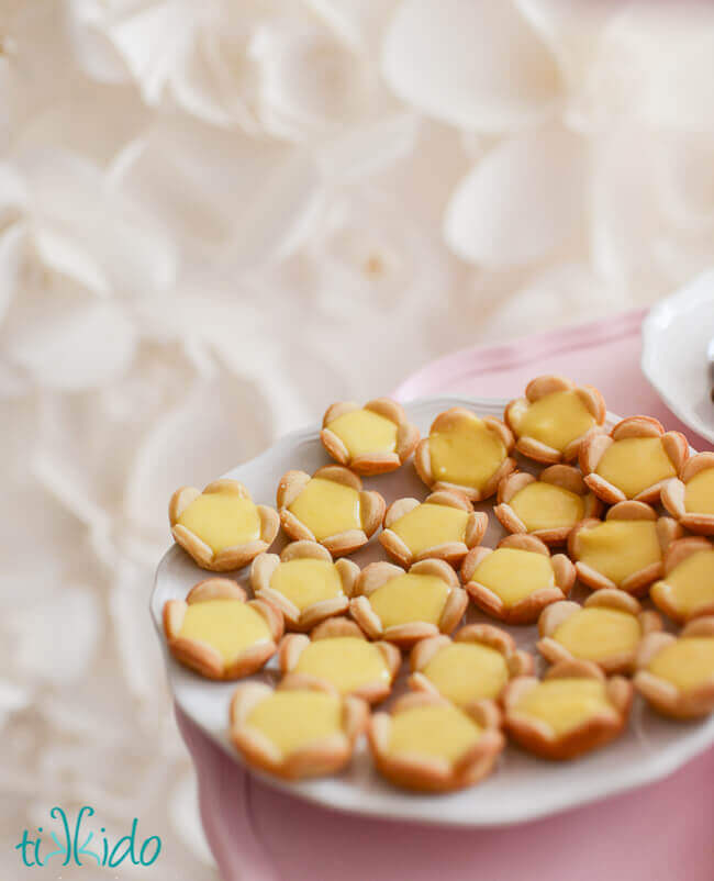 Mini lemon tarts filled with lemon curd on a white plate, in front of a textured paper flower backdrop.