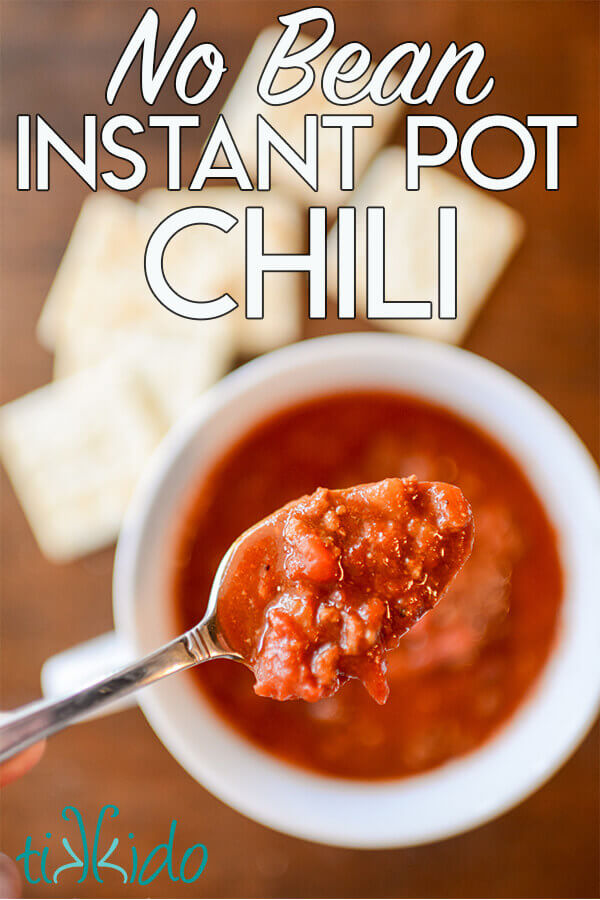 Spoon full of no bean chili made in an Instant Pot pressure cooker, above a white bowl of the chili on a wooden table.
