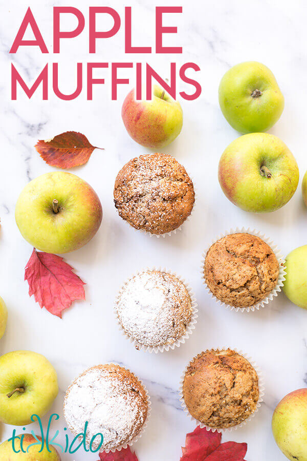 apple muffins surrounded by fresh apples and fall leaves on a white marble background.