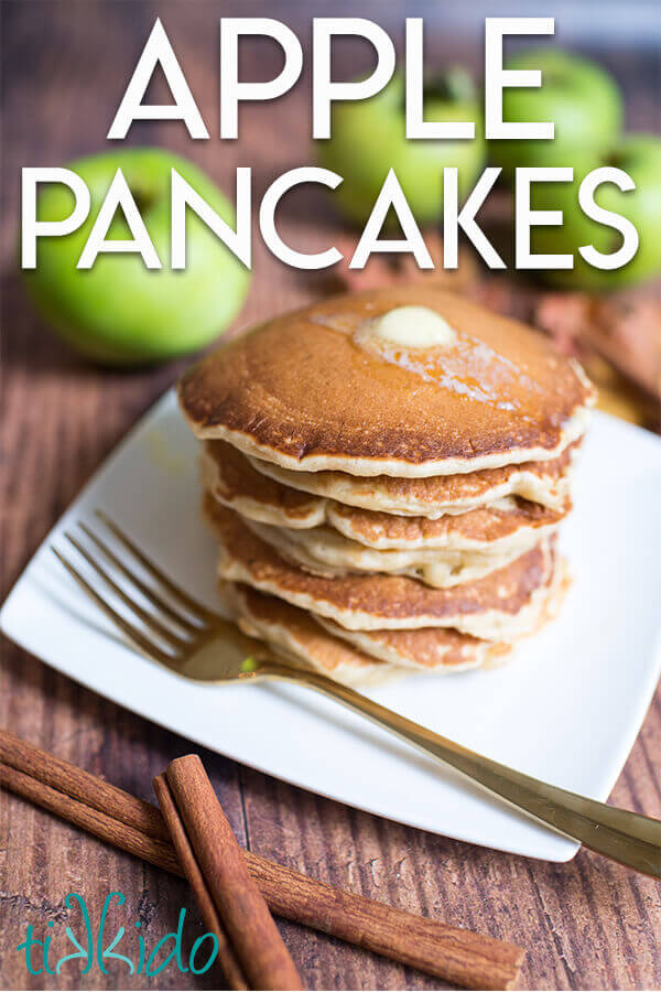 "Stack of apple cinnamon pancakes on a white plate, surrounded by apples and cinnamon sticks, with a text overlay reading ""Apple Pancakes."""