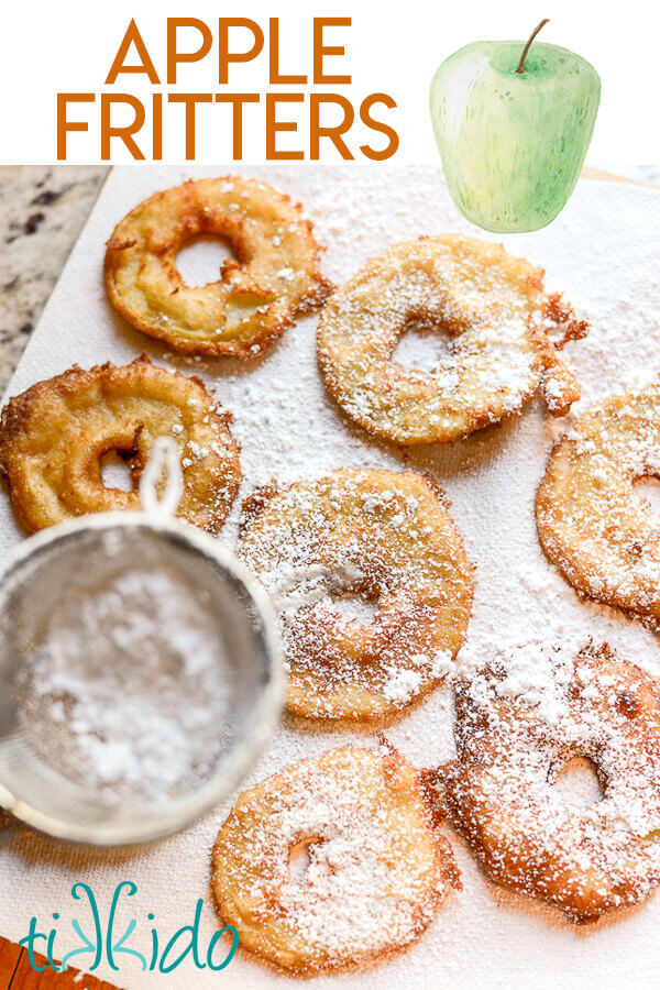 Apple fritter rings being dusted with powdered sugar.