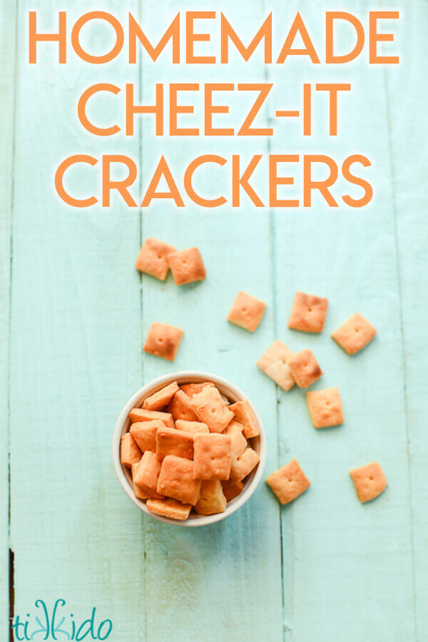 Homemade cheese crackers cut into tiny squares on a turquoise wooden background.