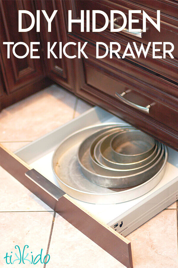 Cake pans in a toe kick drawer under brown kitchen cabinets.