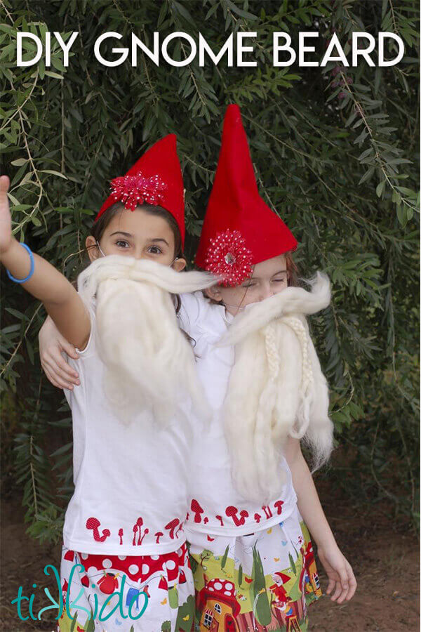 Two little girls hugging, wearing gnome hats and gnome beards.