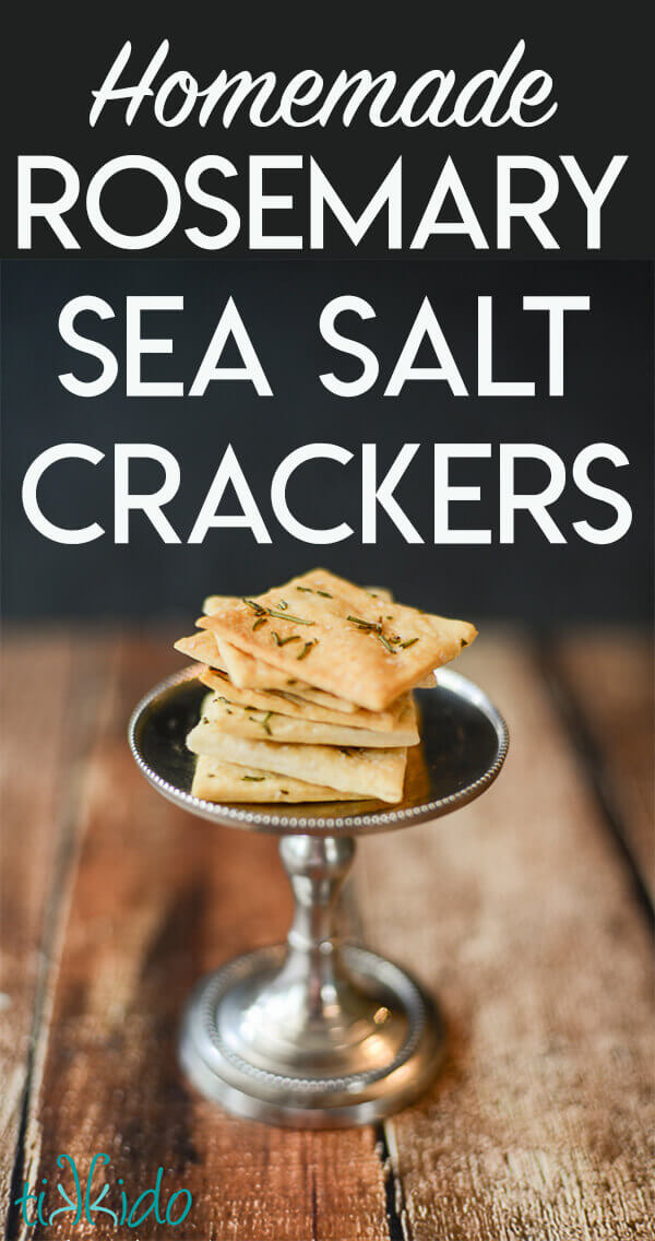 Homemade crackers topped with rosemary and salt stacked on a small silver stand.