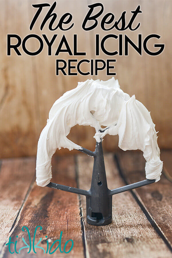 Royal icing on a metal beater standing on a wooden surface.