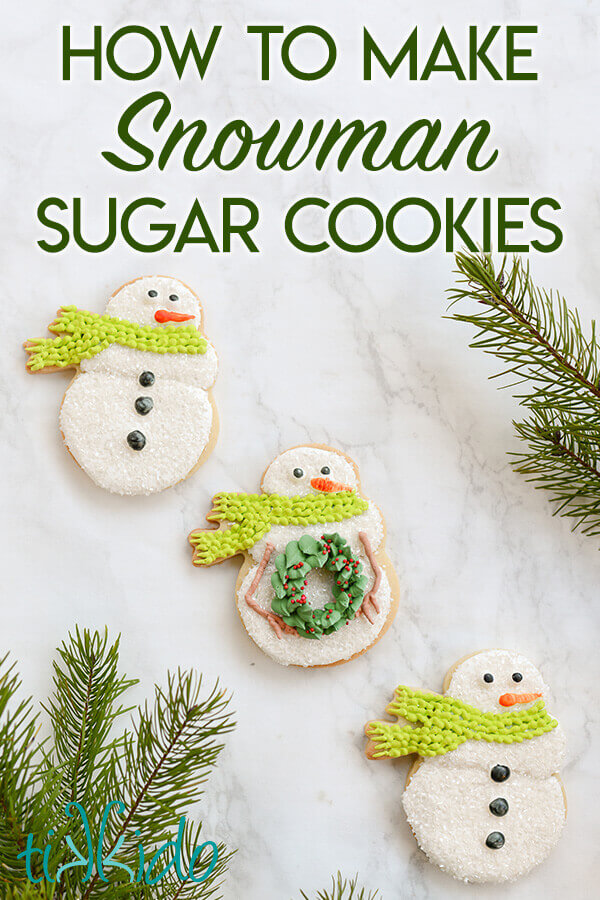 Three snowman sugar cookies  on a white marble background
