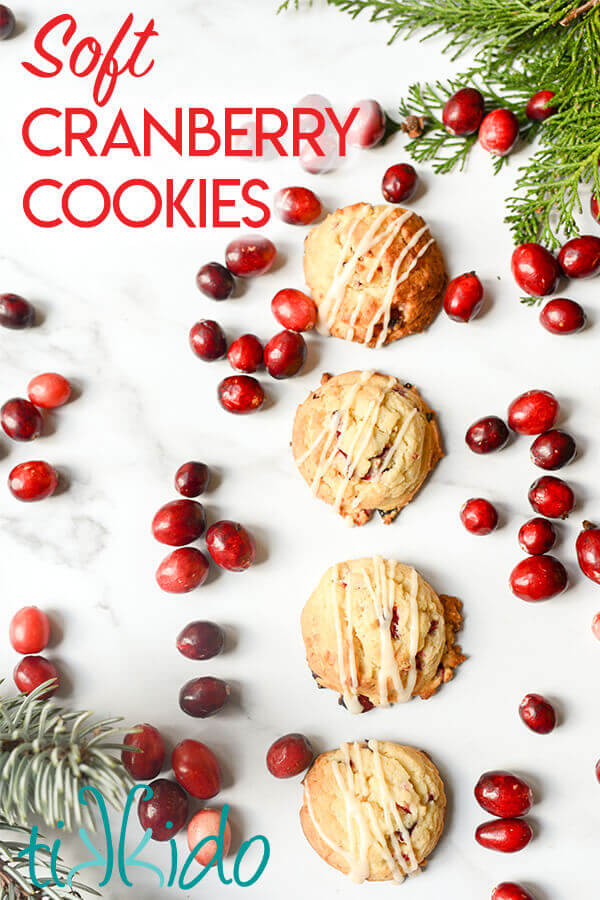 Cranberry cookies surrounded by fresh cranberries on a white marble background.