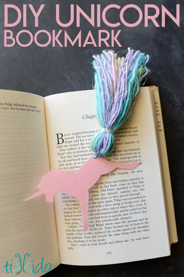 Unicorn bookmark that looks like a running unicorn with a rainbow tassel tail on an open book.