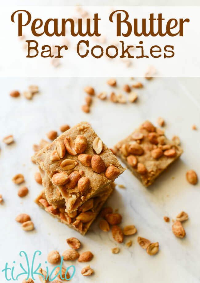 Peanut butter bar cookies on a white marble background surrounded by peanuts.