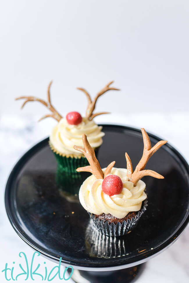 Two reindeer cupcakes on a black cake stand on a white background.