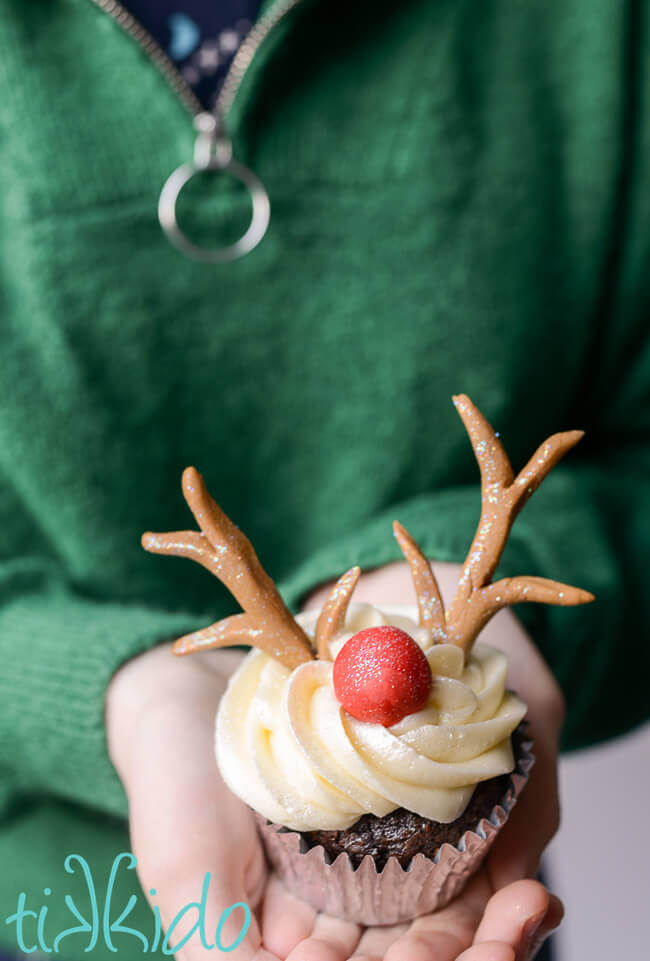 Person wearing a green sweater and holding a reindeer cupcake topped with gum paste reindeer antlers and a red Rudolph nose.