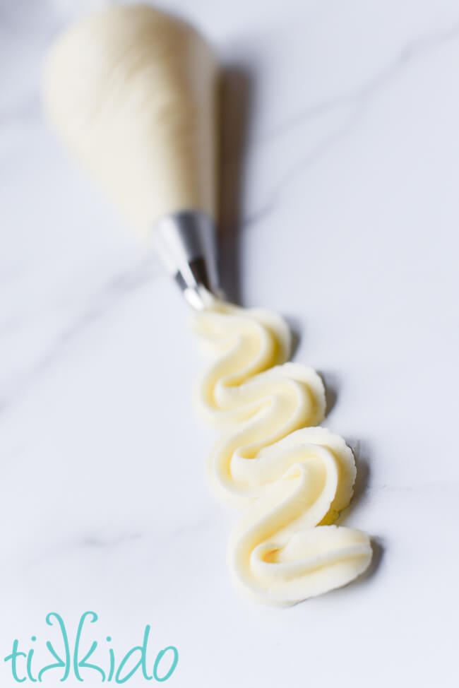 Cream cheese frosting swirled from an icing bag fit with an open star tip.