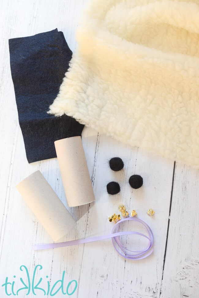 Materials for making Easter Sheep Napkin Rings on a white wooden surface.