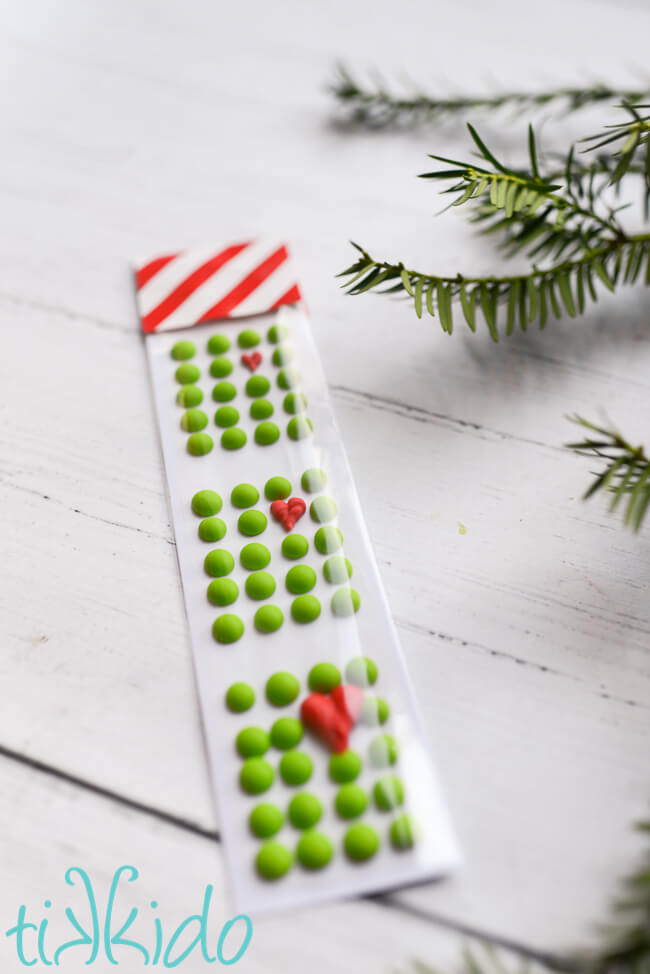 Grinch candy buttons packaged and on a white wooden surface.