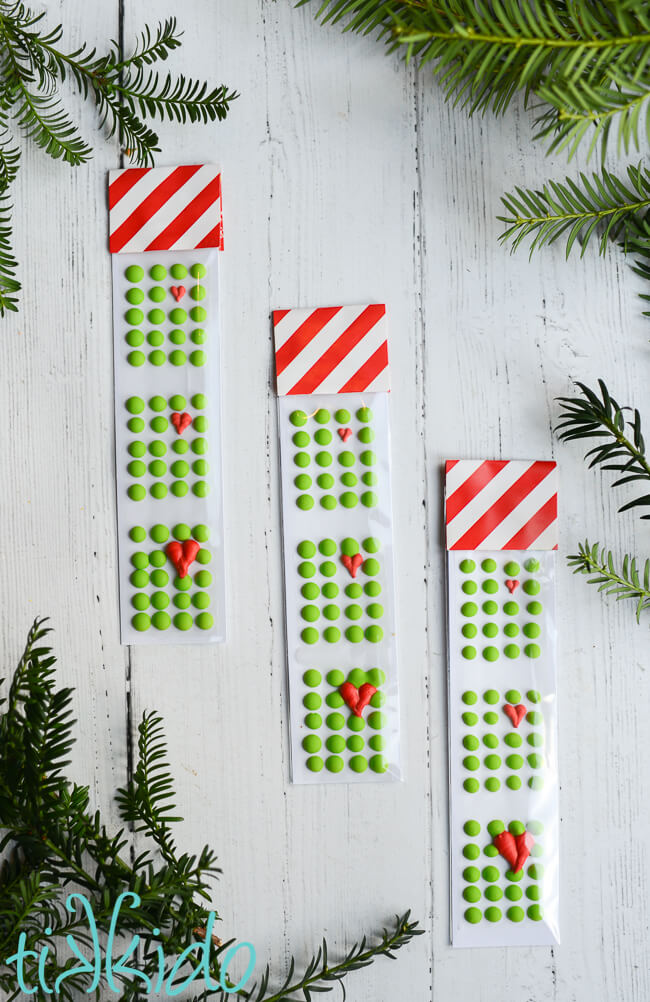 Three packages of Grinch themed homemade candy buttons on a white wooden background.