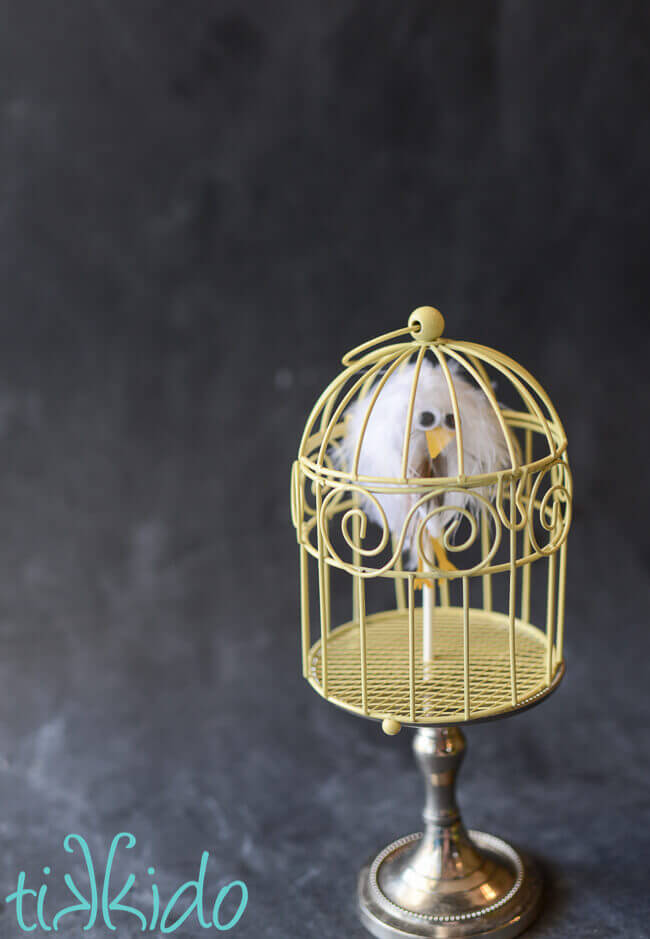 Lollipop that looks like a feather covered owl in a small yellow cage for a Harry Potter party.