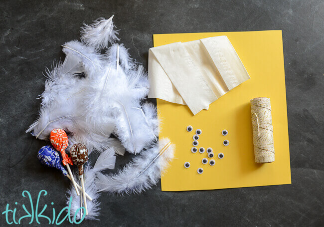 lollipops, feathers, tissue paper, string, yellow paper, and googly eyes on a black background.