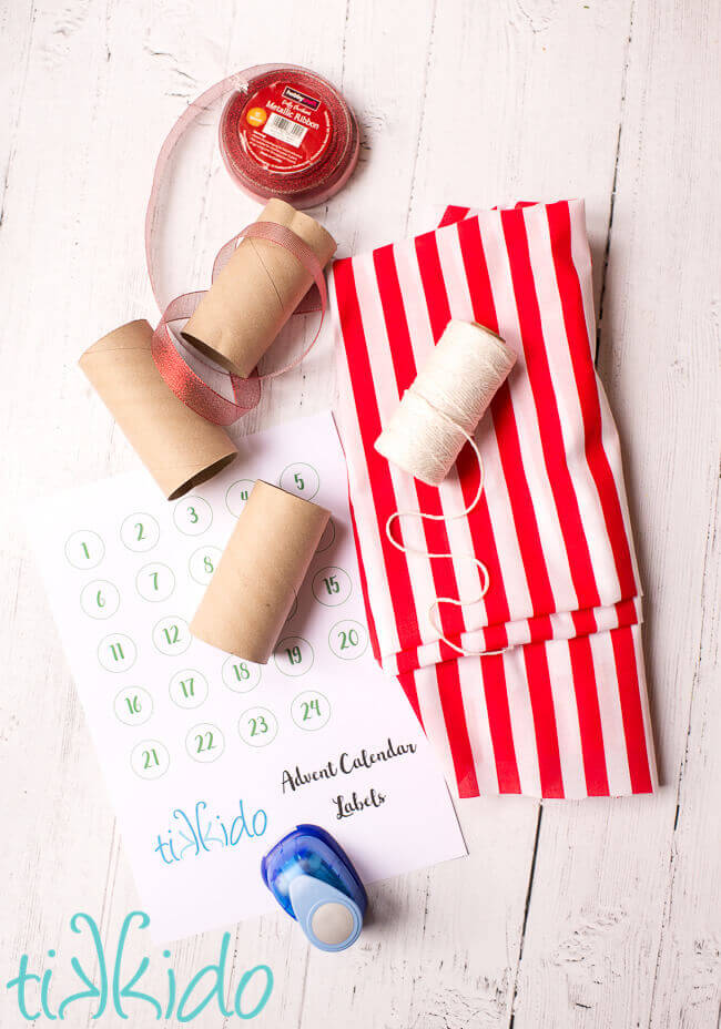 Materials for DIY Advent Calendar garland on a white wooden surface.