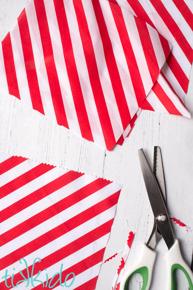 Red and white striped fabric being cut into rectangles with pinking shears for a DIY Advent Calendar.