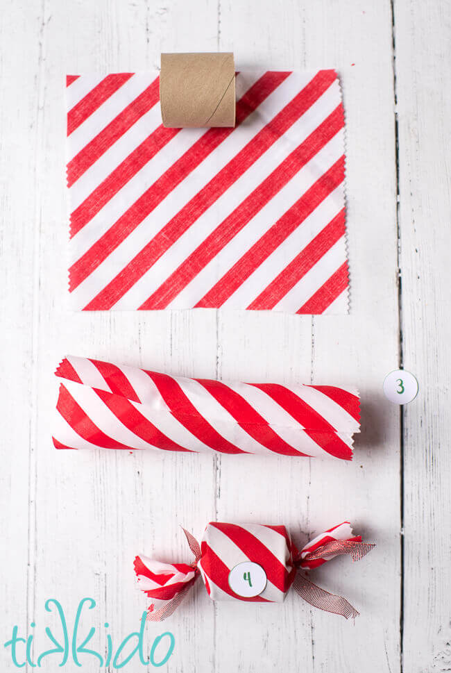 toilet paper tubes being wrapped in red and white fabric to make a DIY Advent Calendar