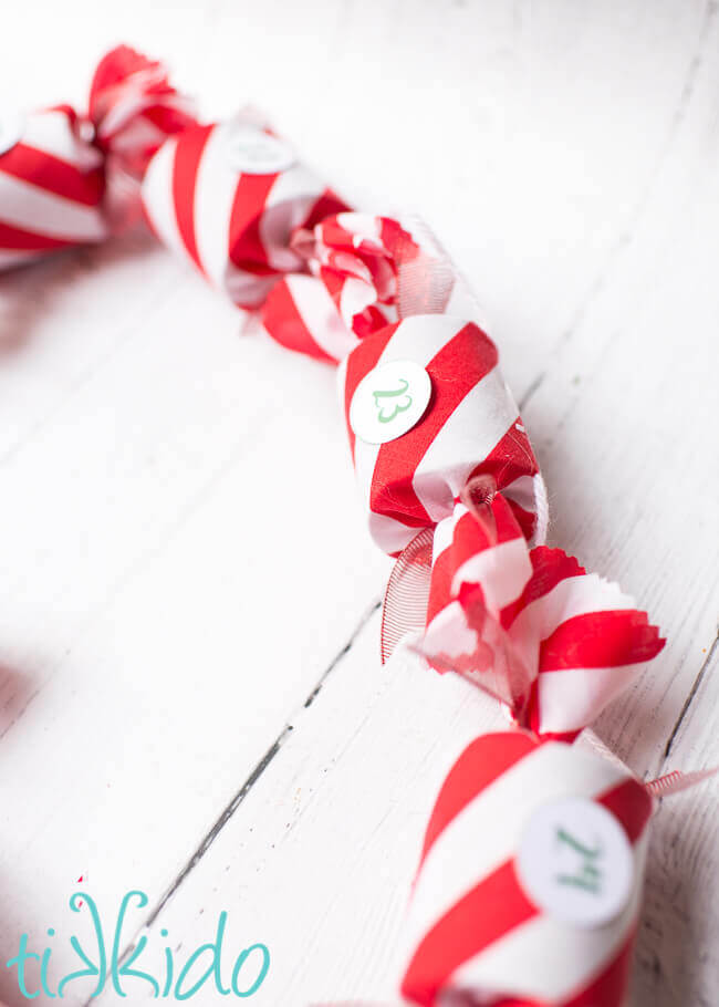 DIY Advent Calendar garland made with red and white fabric on a white wooden background.