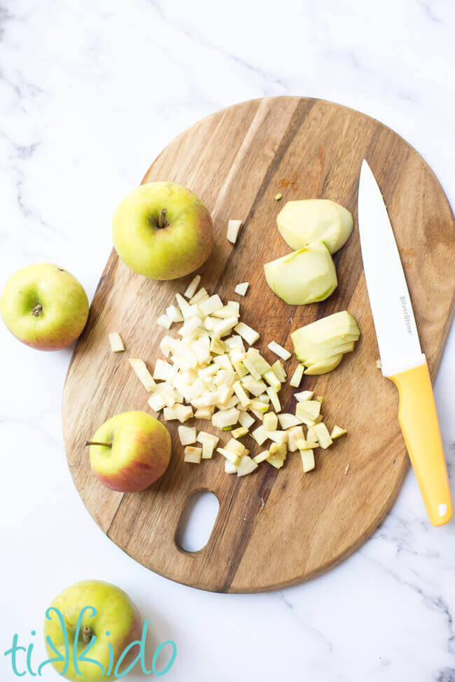 Apples being chopped on a wooden chopping board for apple muffin recipe