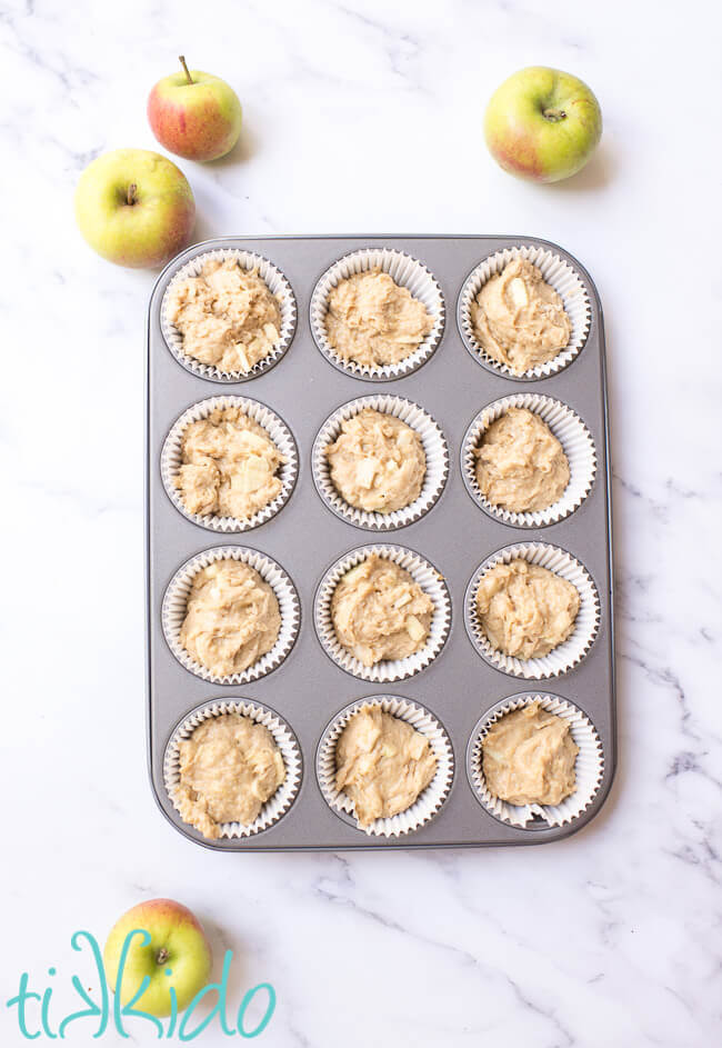 Apple muffin batter, unbaked, in a lined muffin tin, surrounded by fresh apples.