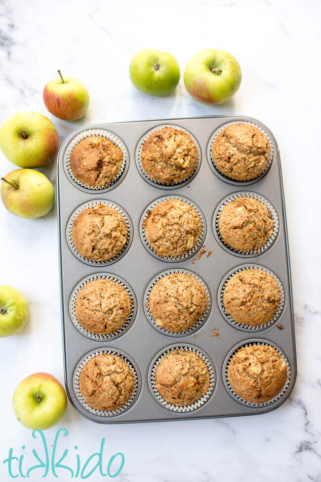 Freshly baked apple muffins in a muffin tin, surrounded by fresh apples.