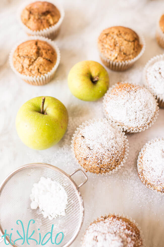 apple muffins being dusted with powdered sugar on a white marble surface.