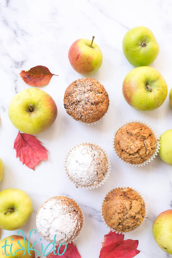 Apple muffins surrounded by fresh apples and fall leaves on a white marble surface.