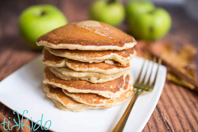 Stack of apple cinnamon pancakes with a pat of butter melting on top, and fresh apples in the background.