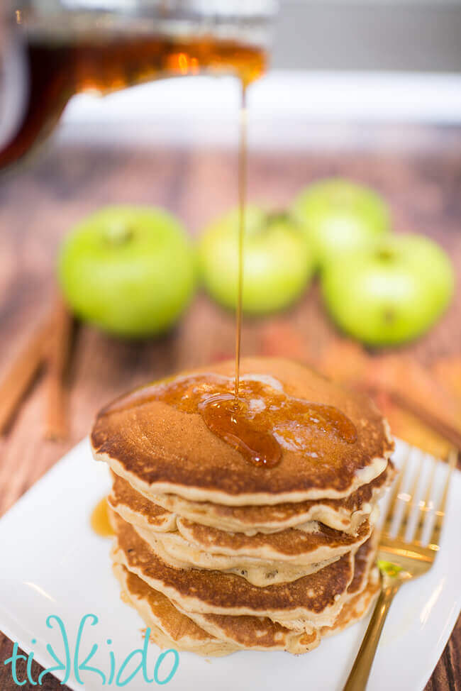 Maple syrup being poured on a stack of apple cinnamon pancakes.