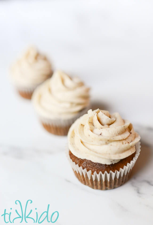 Browned Butter Frosting swirled on three cupcakes sitting in a row.