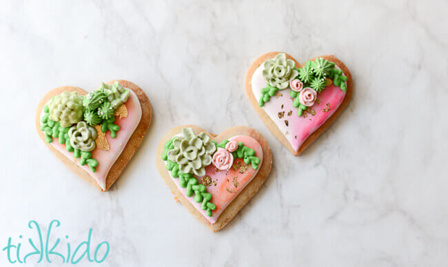 Heart shaped sugar cookies, covered in watercolor painted royal icing, with gold leaf and piped succulents.