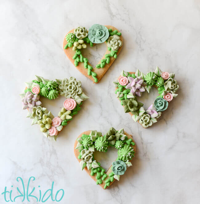 Heart shaped sugar cookies, covered in piped royal icing succulents.