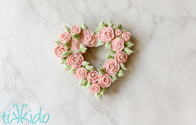 Heart shaped sugar cookie covered in piped royal icing roses and leaves.