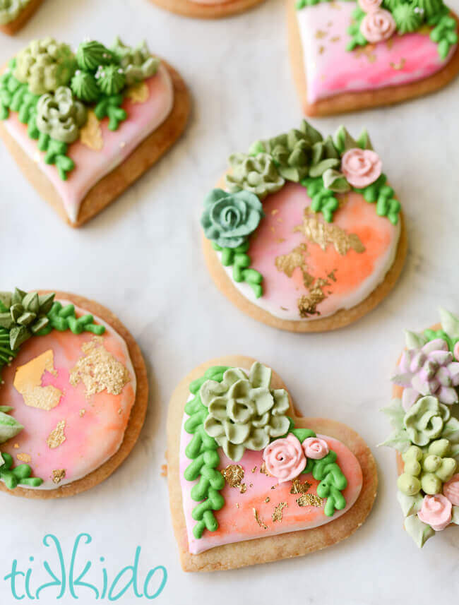 Heart and round shaped sugar cookies, covered in watercolor painted royal icing, with gold leaf and piped succulents.